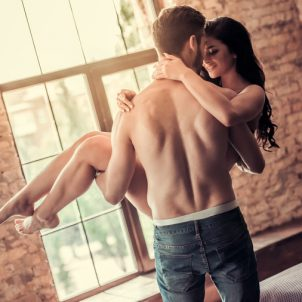 Sexy young couple at home. Handsome topless man is holding smiling woman in his arms